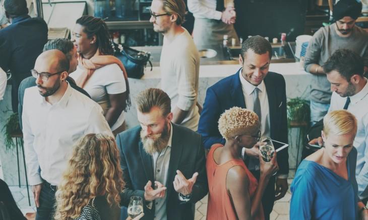 vue plongeante surun groupe de jeunes de 20 ou 30 ans qui échangent et discutent au cours d'un cocktail