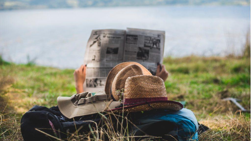 personnage allongé dans l'herbe lisant un journal papier, devant un plan d'eau