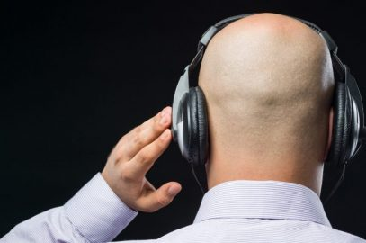 homme chauve de dos, muni d'écouteurs noirs