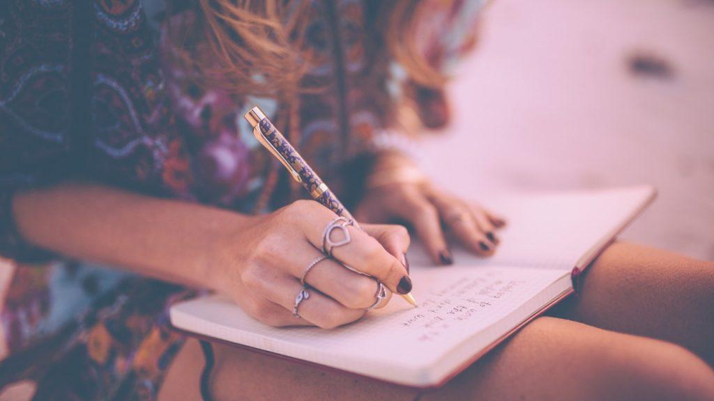eune fille qui écrit sur ses genoux un journal intime