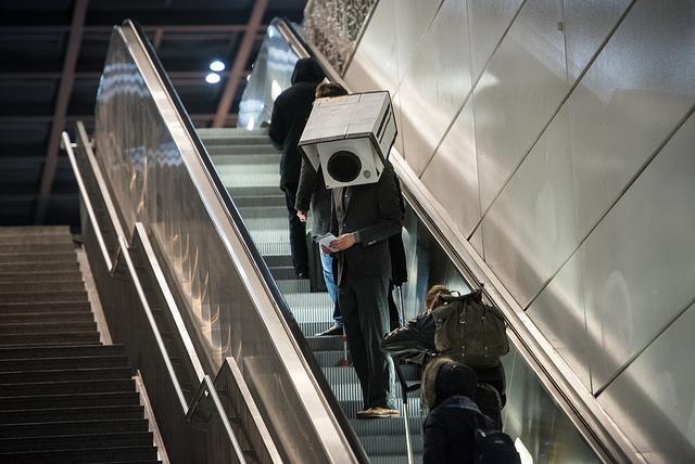 Personne portant une vidéo de surveillance en carton sur sa tête dans des escalators