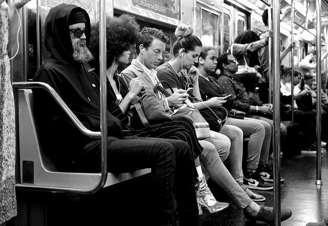 passagers dans le métro, ils ont presque tous des écouteurs aux oreilles et leur smartphone en main