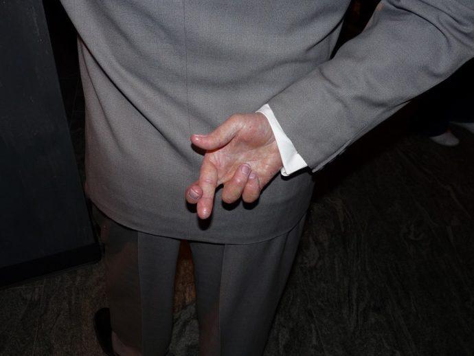 personnage en costume gris, les doigts de la main droite croisés dans le dos