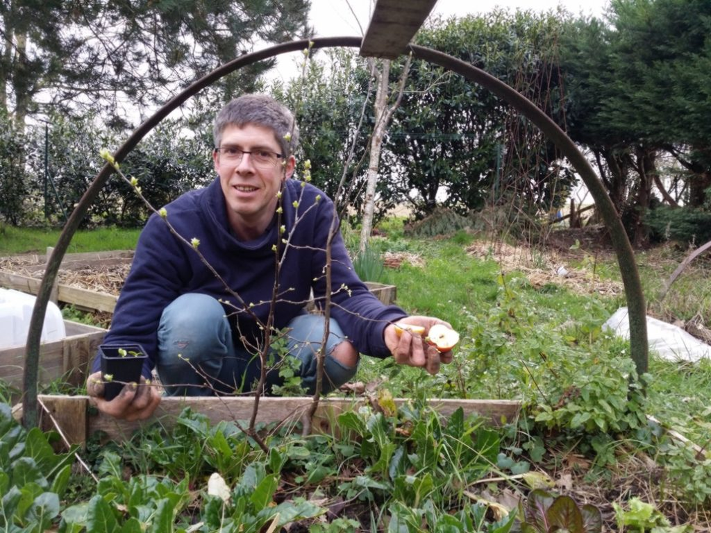 Bertrand souriant accroupi devant une planche végétale de son jardin, montre deux demi-pommes et un petit pot avec un plant. L'image le montre comme entouré par un arceau en demi-cercle métallique probablement support d'une petite serre-tunnel.