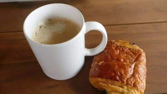 tasse blanche remplie aux 3 quarts de café unpeu mousseux. À ses côtés, un chocopain, sur fond de table en bois clair.